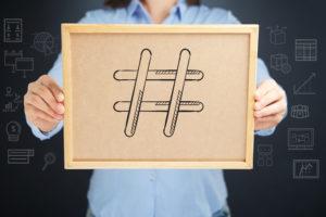 man holding a hashtag cork board